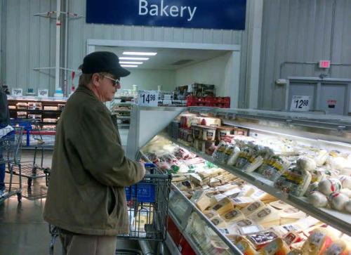 A man wearing sunglasses, staring at cheese.